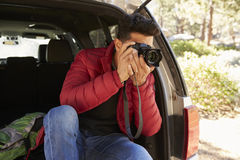 Man sitting in the open back of car taking photos, close up Stock Photo