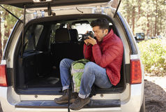 Man sitting in the open back of car taking photos in forest Royalty Free Stock Images