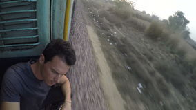 Man sitting by open train entrance during a fast train ride. MUMBAI, INDIA - 3 FEBRUARY 2015: Man sitting by open train entrance during a fast train ride stock video