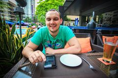 Man sitting at an outdoor cafe table with a phone Royalty Free Stock Images