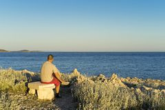 Man sitting outdoors on bench looking at sea in sunset Royalty Free Stock Photography
