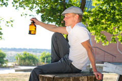 Man sitting outdoors enjoying a drink Stock Images