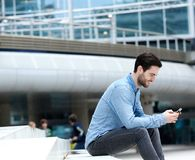 Man sitting outdoors with mobile phone Royalty Free Stock Photo