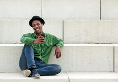Man sitting outdoors with mobile phone. Portrait of a happy young man sitting outdoors with mobile phone stock photography