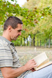 Man sitting outdoors reading a novel Royalty Free Stock Photography