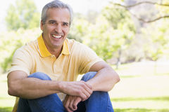 Man sitting outdoors smiling Royalty Free Stock Images