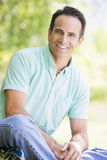 Man sitting outdoors smiling Stock Photo