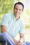 Man sitting outdoors smiling Stock Photo