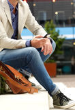 Man sitting outdoors on steps with mobile phone Stock Photo