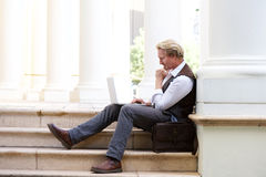 Man sitting outdoors on steps and working on laptop Royalty Free Stock Photos