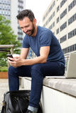 Man sitting outdoors and using mobile phone Stock Photos