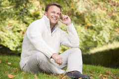 Man sitting outside in autumn landscape. Man sitting outside on grass in autumn landscape Royalty Free Stock Photography