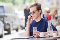 Man Sitting in Outside Coffeehouse Talking on Phone. Young Man Sitting in Outside Coffeehouse Talking on Cell Phone Stock Images