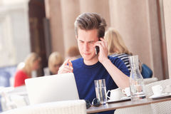 Man Sitting in Outside Coffeehouse Talking on Phone Stock Photography