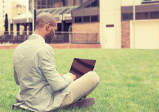 Man sitting outside corporate office working on laptop computer. Young business man sitting on a lawn green grass outside corporate office working on laptop Royalty Free Stock Photography