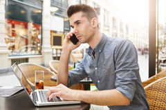 Man sitting at outside restaurant with drink working with laptop. Side portrait of man sitting at outside restaurant with drink working with laptop Royalty Free Stock Images