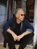 Man sitting outside wearing sunglasses Stock Photo