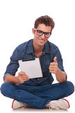 Man sitting with pad shows ok. Casual young man sitting in the lotus pose and showing ok gesture while holding a tablet in his hands and smiling to you. isolated Stock Images