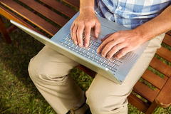 Man sitting on park bench using laptop Stock Images