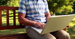 Man sitting on park bench and using laptop stock video footage