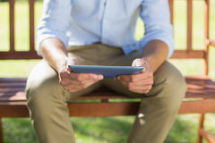 Man sitting on park bench using tablet Stock Photo