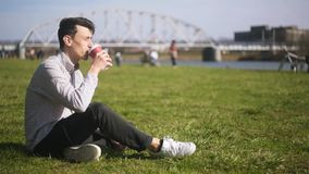 The man sitting in the park on grass, enjoying the sunshine, drinking coffee. A man is sitting near a river, people are walking. Around the background. Lucky stock video footage