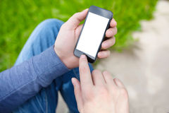 Man sitting in the park and holding phone with isolated screen Royalty Free Stock Images