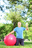 Man sitting in park with pilates ball Royalty Free Stock Photos