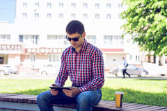 The man sitting in the park with tablet in hand, summer in glasses and a shirt in the woods outdoors, reading social Stock Photos