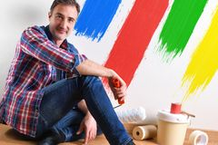 Man sitting on parquet and wall painted with colors detail stock photos