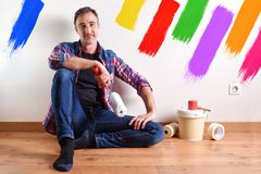 Man sitting on parquet and wall painted with seven colors royalty free stock photography