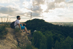 Man sitting on the peak alone with his minds. Clody wheather Stock Photography