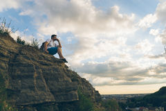 Man sitting on the peak alone with his minds. Clody wheather Royalty Free Stock Image