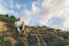 Man sitting on the peak alone with his minds. Clody wheather Royalty Free Stock Images