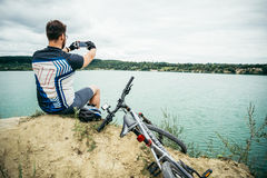 Man sitting on the peak of the hill with bicyle and taking picture of the view. Man sitting alone on the peak of the hill with bicyle and taking picture of the Royalty Free Stock Photo