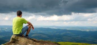 Man sitting on the peak of the mountain. Man sitting on the top of the mountain. Cloudy royalty free stock image