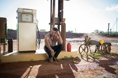 Man sitting at petrol pump station Royalty Free Stock Images