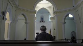 Man sitting in a pew at Church and meditating, faith and religion concept. Man sitting pew at Church and meditating, faith and religion concept stock footage