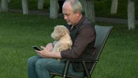 The man is sitting with the phone and holding a dog stock video footage