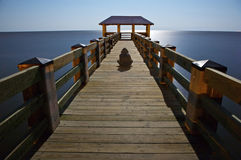 Man Sitting on Pier. A single man sitting on a pier at night. Long expsosure and moving subject creates a patially 'invisible' silhouette royalty free stock photography