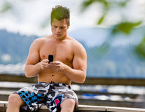 Man sitting on pier text messaging Stock Photography