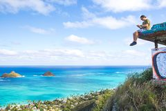 Young man sitting on pillbox over looking Lanikai texting on a c. Man sitting on pillbox over looking Lanikai texting on a cell phone loving sitting on top of Stock Photo