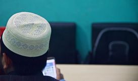 Man sitting in a place wearing white caps. A young man wearing white religious caps sitting in a place unique photo stock images