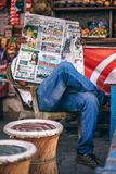 Man Sitting on Plastic Armchair Reading Newspaper Royalty Free Stock Photo
