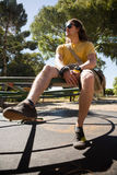 Man sitting on a playing equipment in the park. Thoughtful man sitting on a playing equipment in the park Stock Image