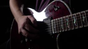 Man is sitting and playing the guitar in a dark room. Close up. 4K stock video footage