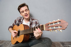 Man sitting and playing on guitar Stock Photo
