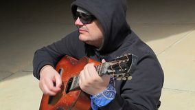Man sitting and playing guitar stock footage