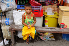 A man sitting and playing at the local market in Bangkok Stock Photo