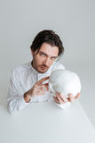 Man sitting and pointing finger at fake skull in hands Royalty Free Stock Images
